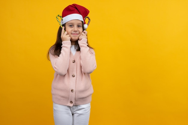 Young girl in santa's christmas cap with candy in her hands on a yellow background