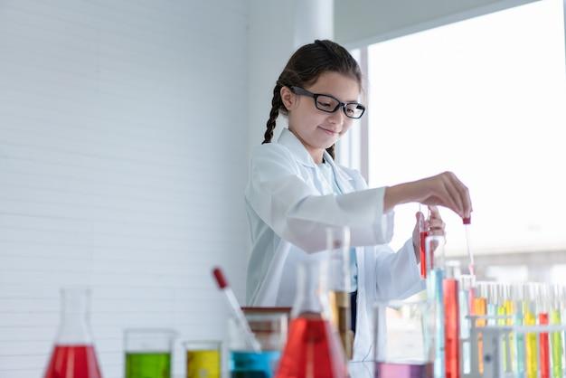 実験室のガラス管で化学実験を行う少女科学者
