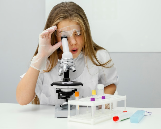 현미경을 사용하는 어린 소녀 과학자