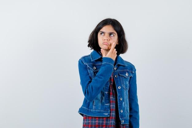 Молодая девушка почесывает лицо, смотрит вдаль в клетчатой рубашке и джинсовой куртке и выглядит задумчиво. передний план.