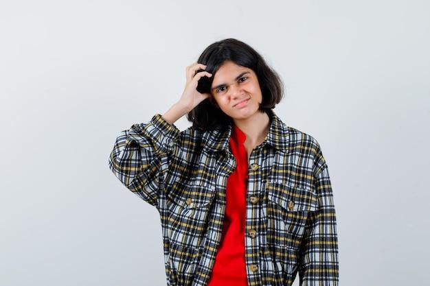 チェックのシャツと赤いtシャツで頭を掻いて真剣に見える少女。正面図。