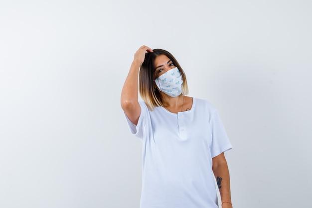 白いtシャツとマスクで頭を掻き、物思いにふける少女。正面図。
