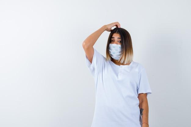 Молодая девушка почесывает голову в белой футболке и маске и выглядит задумчиво. передний план.
