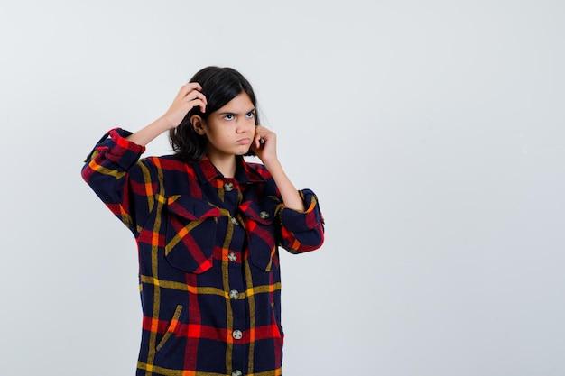Giovane ragazza che si gratta la testa, mette la mano sulla guancia in camicia a quadri e sembra pensierosa. vista frontale.