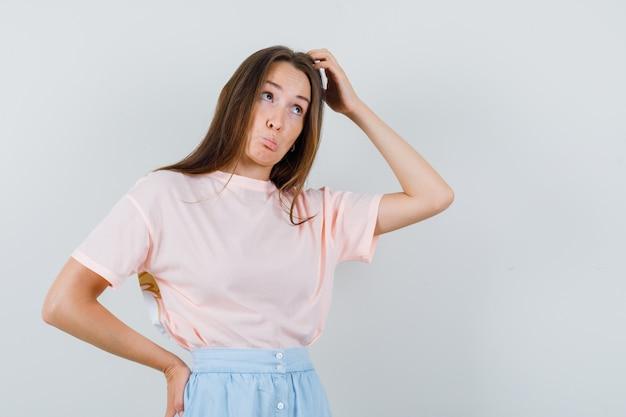 Giovane ragazza grattarsi la testa in t-shirt, gonna e guardando esitante, vista frontale.