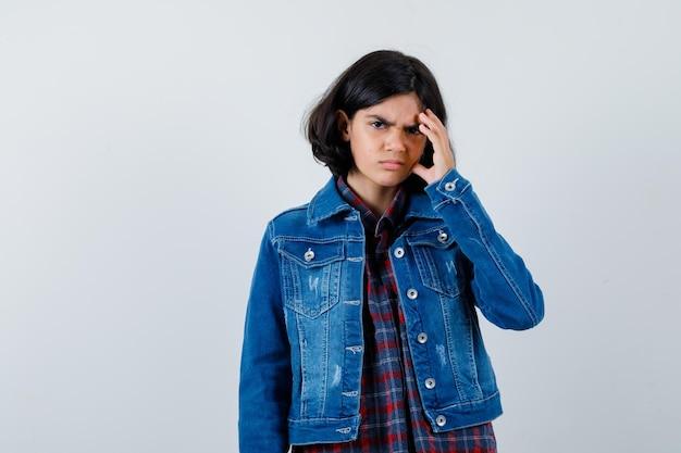 어린 소녀가 머리를 긁적이며 체크 셔츠와 진 재킷을 입고 생각에 잠긴 채 앞을 바라보고 있습니다.
