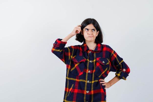 Giovane ragazza che si gratta la testa mentre tiene la mano sulla vita in camicia a quadri e sembra pensierosa, vista frontale.