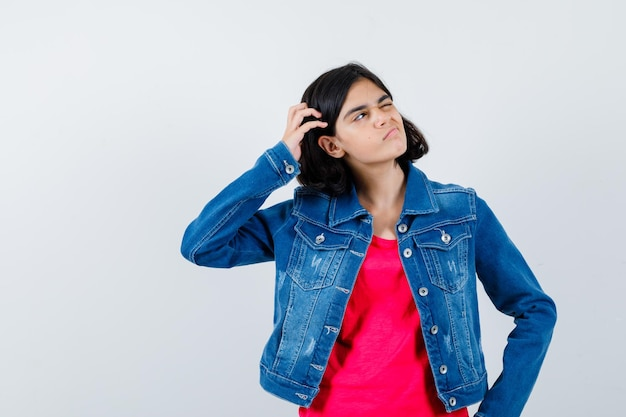Young girl scratching head while holding hand on waist, thinking about something in red t-shirt and jean jacket and looking pensive , front view.