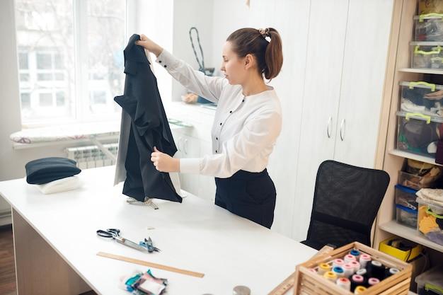 어린 소녀 재봉사가 옷을 바느질하기 위해 직물 샘플을 선택합니다.