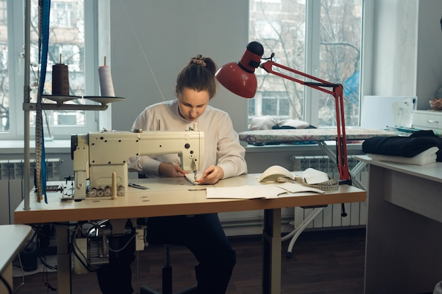 그녀의 작업장에서 재봉 작업을하는 동안 어린 소녀 재봉사