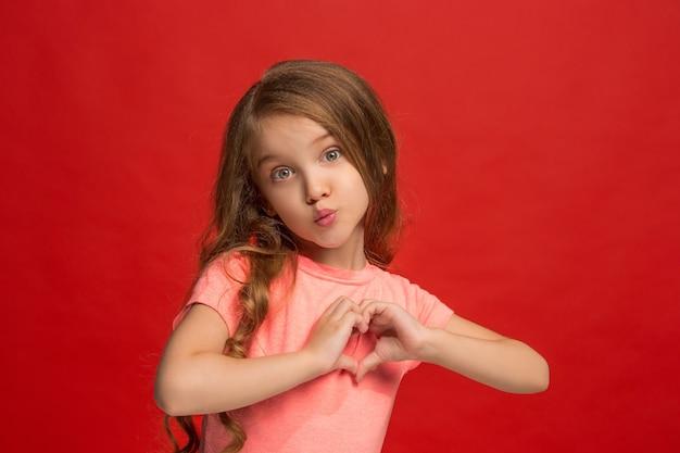 Молодая девушка отправляет поцелуй и делает знак сердца руками