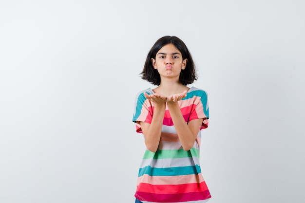 Young girl sending kisses in colorful striped t-shirt and looking pretty , front view.