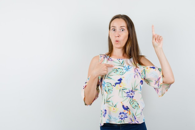 Young girl in shirt, jeans pointing at herself with finger up and looking puzzled , front view.