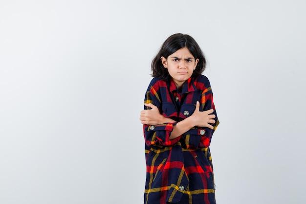 チェックのシャツを着て寒さから震え、イライラしている若い女の子。正面図。