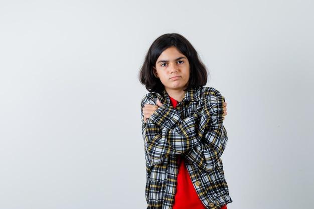 Молодая девушка в клетчатой рубашке и красной футболке дрожит от холода и выглядит серьезной. передний план.