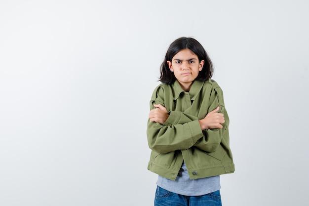 Молодая девушка дрожит от холода в сером свитере, куртке цвета хаки, джинсовых брюках и выглядит раздраженной, вид спереди.