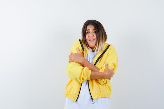 Молодая девушка дрожит от холода в белой футболке, желтой куртке и выглядит измученной, вид спереди.
