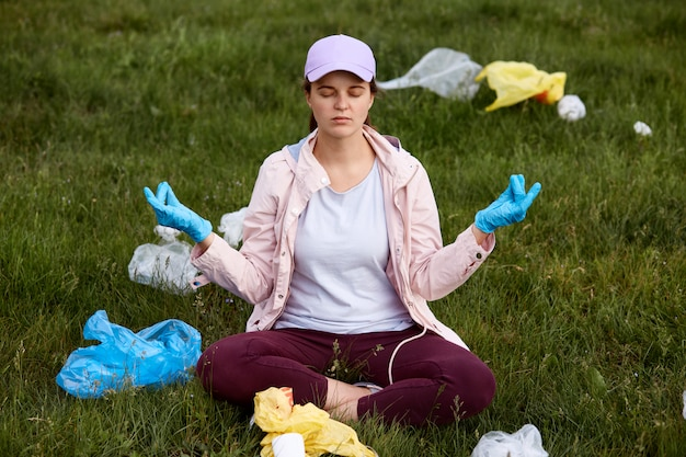 野外で泥にショックを受け、落ち着こうとする、瞑想する、非常に動揺する、ゴミに囲まれる、目を閉じておく、生態系の問題で悲しい少女。