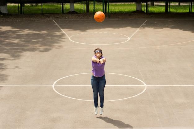 彼女は屋外のバスケットボールコートで練習しながらフープとネットでバスケットボールを撃つ少女