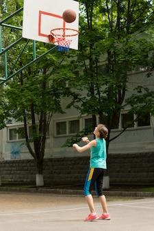 バスケットボールでゴールを撃つ少女