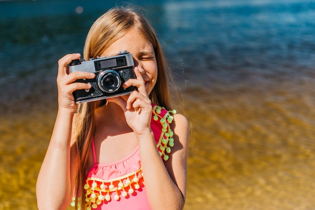 Young girl shooting on camera against background of sea