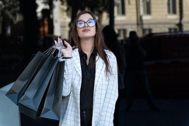 검은 배경에 손에 쇼핑백과 어린 소녀 쇼핑객. 블랙 프라이데이, 판매, 할인.