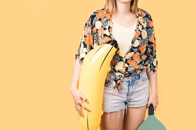 Young girl in shorts and flowered shirt holding inflatable banana on yellow background