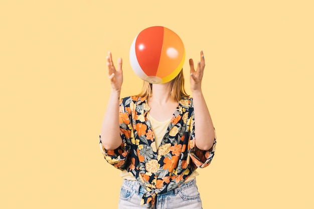 Young girl in shorts and flowered shirt throwing colorful beach ball on yellow background