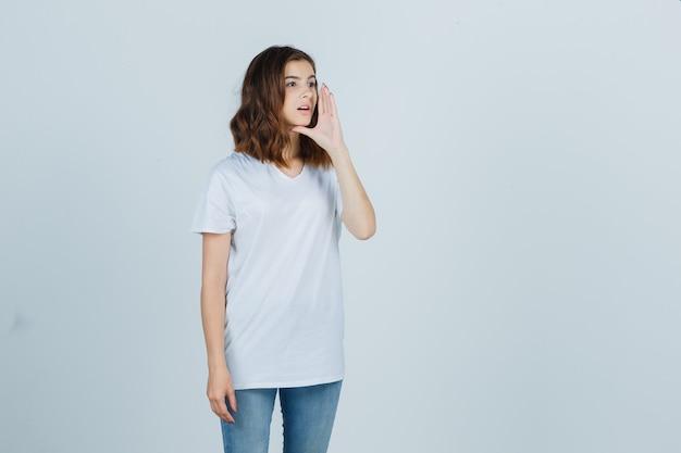 Молодая девушка кричит кому-то в белой футболке, джинсах и выглядит мило, вид спереди.