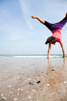 Young girl show an acrobatic on the beach.