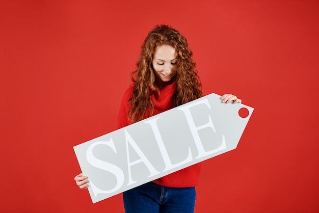Молодая девушка показывает баннер зимней распродажи