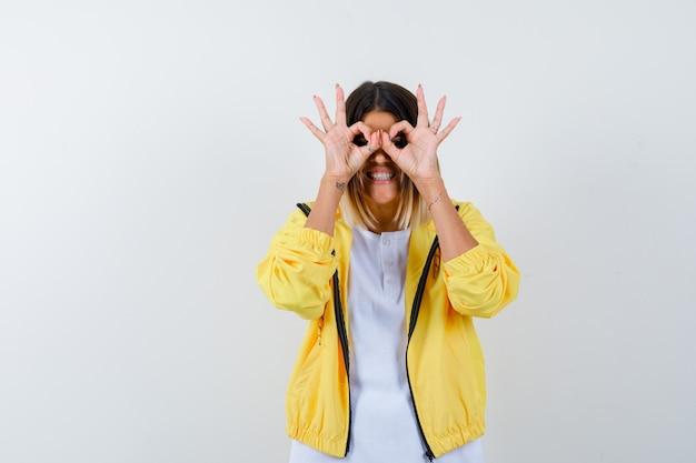 Молодая девушка показывает жест в бинокль в белой футболке, желтой куртке и выглядит весело. передний план.