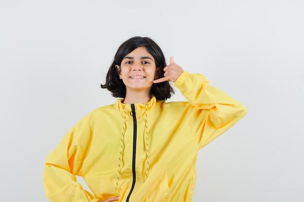 黄色いボンバージャケットを着て幸せそうに見える若い女の子が私をジェスチャーと呼んでいます。