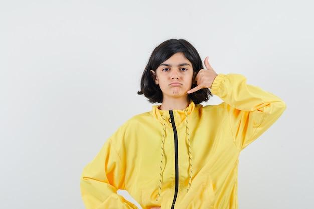 黄色いボンバージャケットを着たジェスチャーで真面目な顔をしている若い女の子。