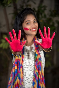 Young girl showing colorful palm and celebrating holi with color splash