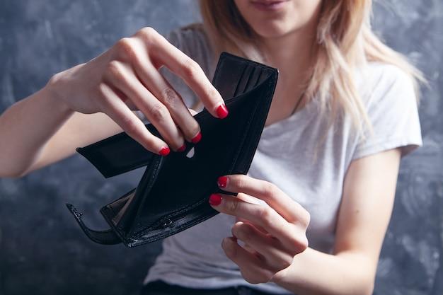 빈 지갑을 보여주는 어린 소녀