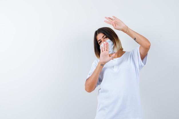 Молодая девушка показывает жест четырьмя пальцами и знак остановки в белой футболке и маске и выглядит уверенно, вид спереди.