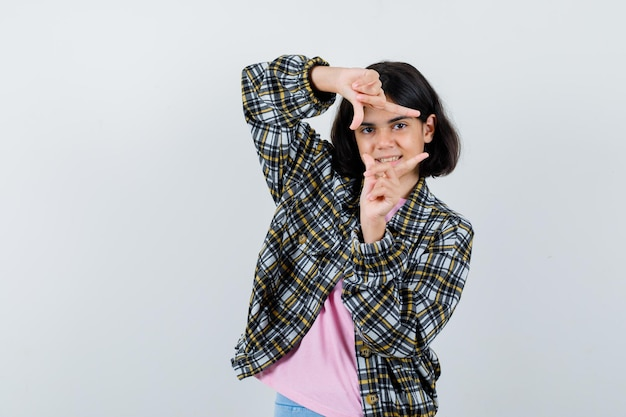 Young girl showing frame gesture in checked shirt and pink t-shirt and looking cute. front view.