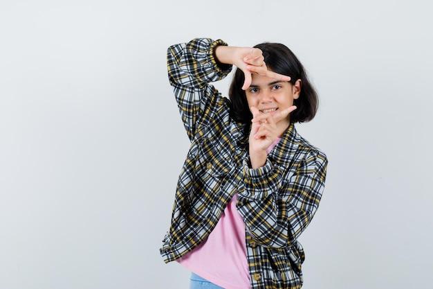 Молодая девушка показывает жест кадра в клетчатой рубашке и розовой футболке и выглядит мило. передний план.