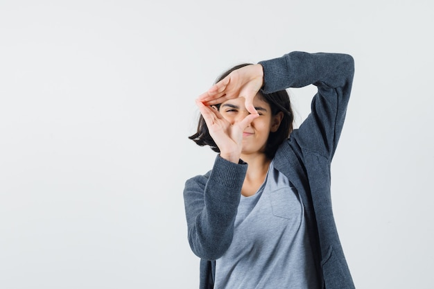 Young girl showing frame gesture in light gray t-shirt and dark grey zip-front hoodie and looking cute ,