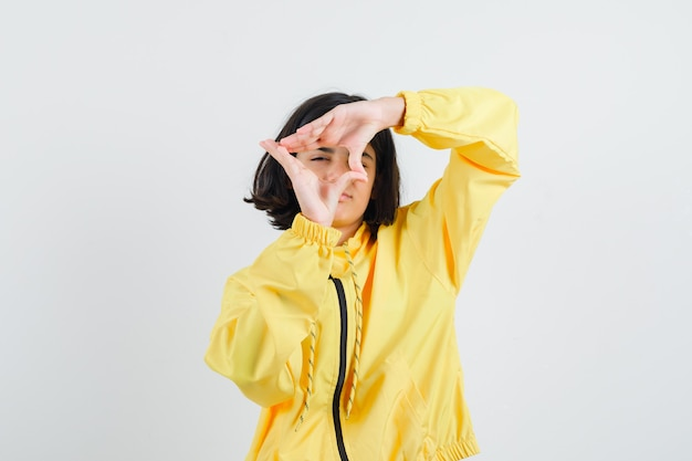 Young girl showing frame gesture in yellow bomber jacket and looking serious.
