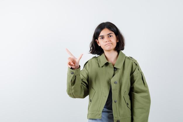 灰色のセーター、カーキ色のジャケット、ジーンズのパンツで銃のジェスチャーを示し、楽観的に見える若い女の子、正面図。