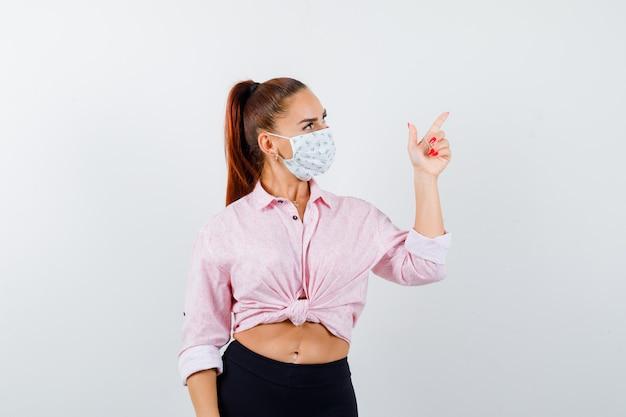 Молодая девушка показывает жест пистолета в розовой блузке, черных штанах, маске и выглядит очаровательно, вид спереди.