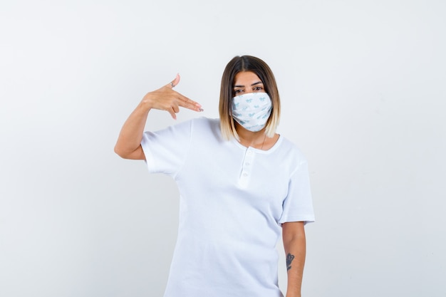 어린 소녀 흰색 t- 셔츠, 마스크에 총 제스처를 보여주는 자신감을 찾고. 전면보기.