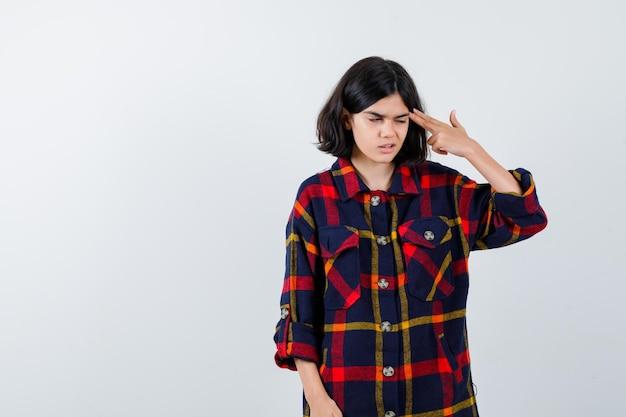 Молодая девушка показывает жест пистолета возле головы, гримасничает в клетчатой рубашке и выглядит серьезным, вид спереди.