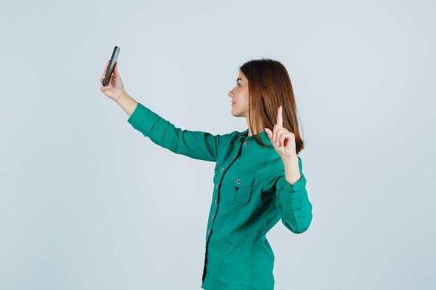 Ragazza che mostra il gesto della pistola mentre si effettua la videochiamata in camicetta verde, pantaloni neri e sembra carina, vista frontale.