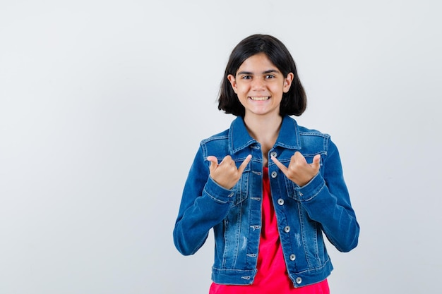 Giovane ragazza che mostra gesti di pistola, sorridente in maglietta rossa e giacca di jeans e sembra carina. vista frontale.