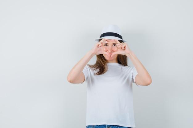 Ragazza che mostra il gesto del cuore in maglietta bianca, cappello e sguardo allegro. vista frontale.