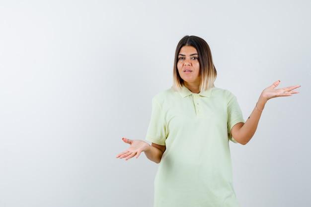 Ragazza che mostra gesto impotente in maglietta e guardando perplesso, vista frontale.