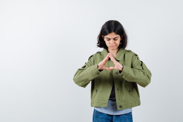 Giovane ragazza che mostra gesto di assicurazione in maglione grigio, giacca kaki, pantaloni jeans e sguardo serio, vista frontale.